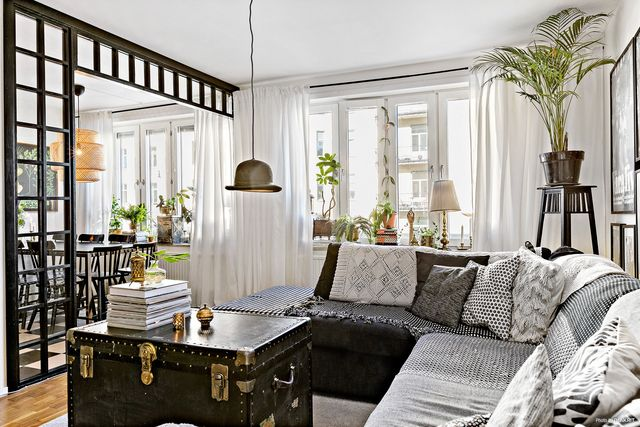 With its checkered floor kitchen and its black glazed partition this swedish apartment is out of the ordinary the decoration is both vintage and ethnic