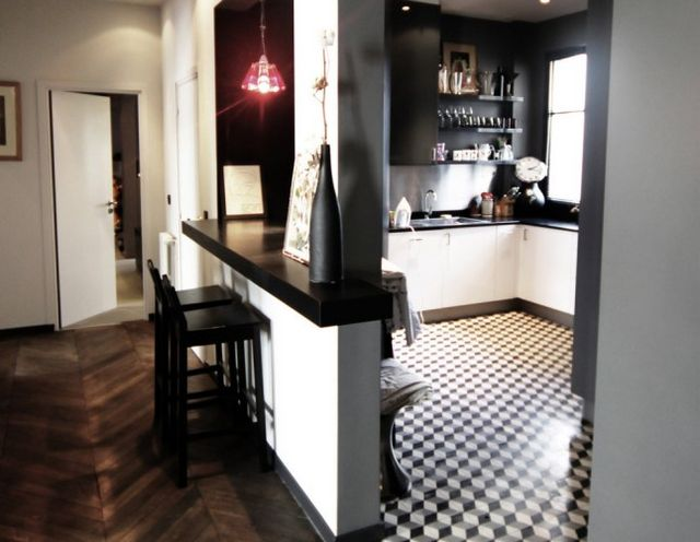 The decoration emphasizes black and white and highlights the old parquet floor in the kitchen cement tiles have been laid on the floor adding charm to